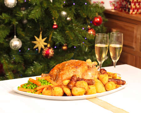 A platter containing a christmas dinner with a christmas tree in the background photo