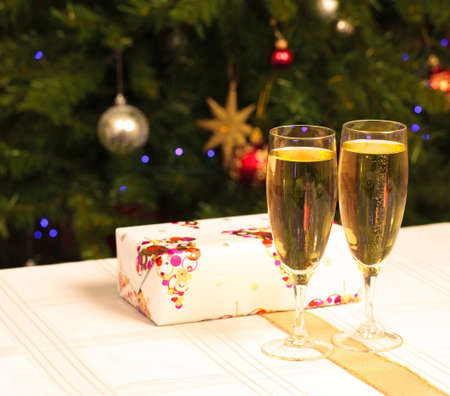 Two wine glasses with a present behind them and a christmas tree in the background