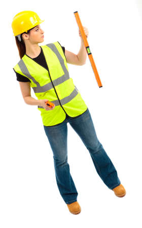 A females dressed in a high visibility jacket holding a spirit level on isloated white background