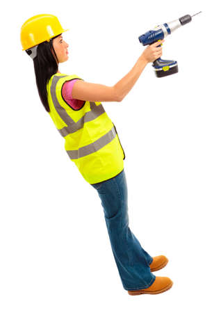A females dressed in a high visibility jacket holding a cordless drill on isloated white background