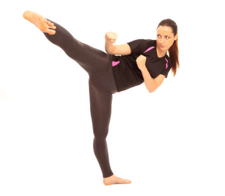 kung fu: A young female dressed in gym clothes performing a martial arts kick on isolated white background