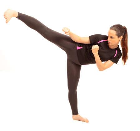 coup de pied: Une jeune femme v�tue de v�tements de sport effectuant un coup d'arts martiaux sur fond blanc isol�