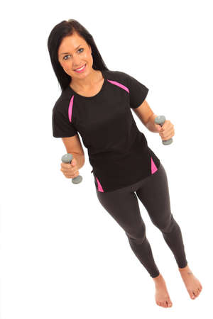 A young female dressed in gym clothes performing dumbell fly exercise on isolated white background