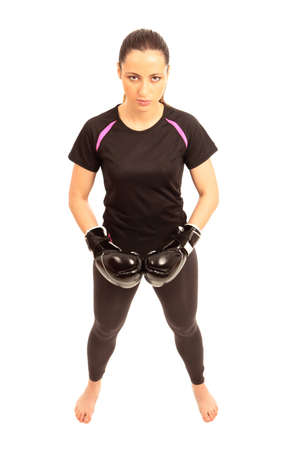 A young female wearing black boxing gloves on an isolated white background Stock Photo