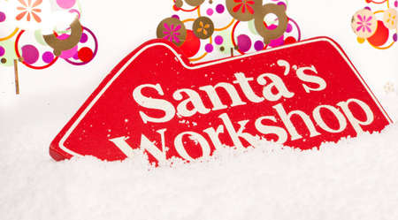 A red sign showing the way to santas workshop sat in snow Stock Photo