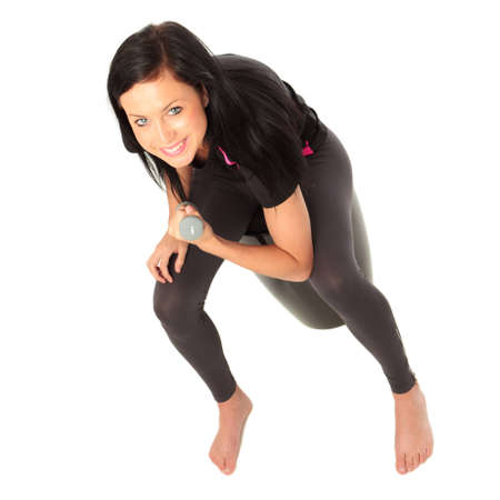 A young female dressed in sports clothes sitting performing a dumbell concentration curl exercise Stock Photo