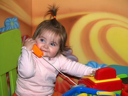 1 year old  girl speaking by toy phone. Very colourful and positive photo.