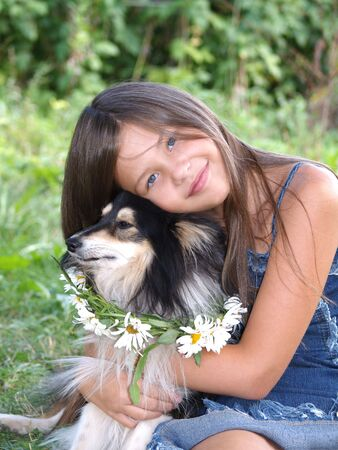 Long haired smiling girl set with tricolour (black-white with tan) Sheltie. Dog has nice necklace from white daisies around his neck. photo