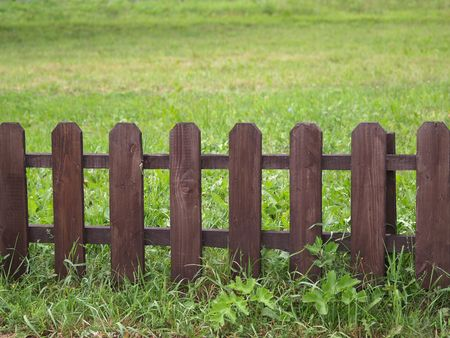 fenced: Wooden fence on green grass lawn