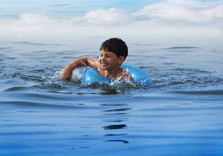 青い水で泳いでいる少年