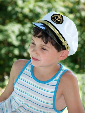 Boy in captains peak-cap, smiling in sunny summer day Stock Photo