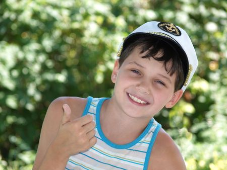 Young boy showing OK and smiling, in captains peak-cap Stock Photo