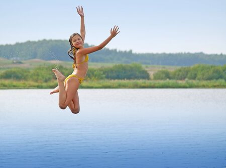 Young girl in bikini jumping above water smooth surface
