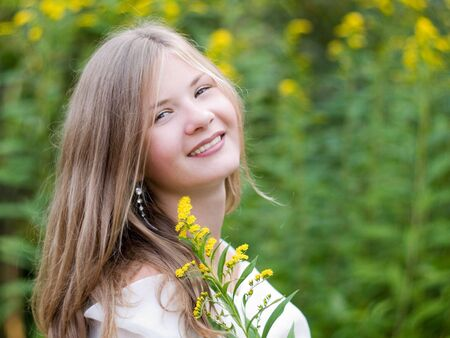 Happy smiling long haired beautiful girl with yellow flower