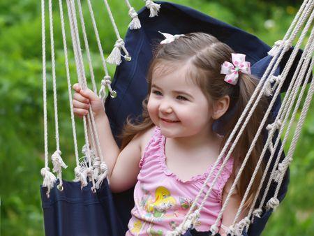 Nice little girl shaking in blue hammock  Stock Photo