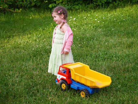 Little girl standing on green lawn with toy truck       Stock Photo