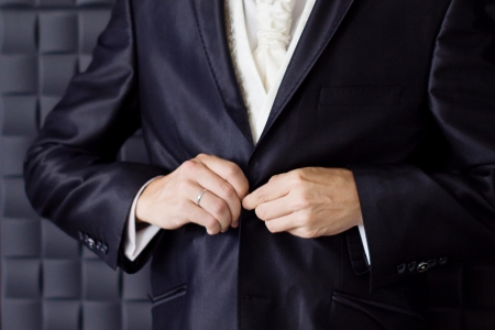 Groom buttoning a jacket