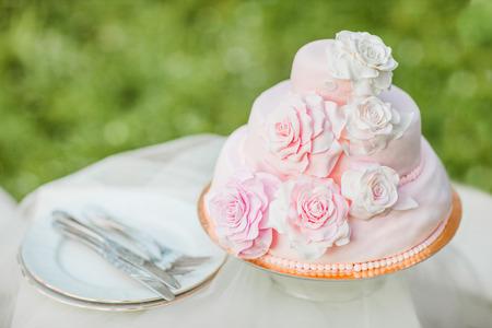 ピンクと白のウエディング ケーキ mastice ロゼット飾られています。ケーキは、自然の緑のぼやけた背景の前にテーブルの上です。結婚式の料理の例 写真素材