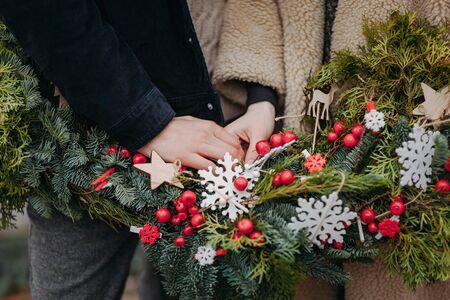 木製と赤いベリーの装飾とクリスマスリースの背景に手を握る愛するカップル