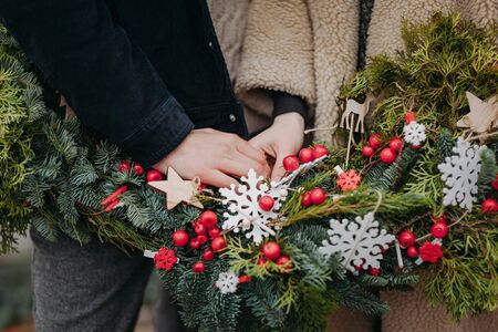 Loving couple holding hands on the background of the Christmas wreath with wooden adn red berries decoration