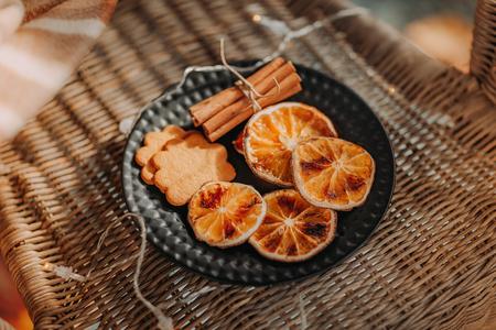 オレンジ、ジンジャーブレッドクッキー、シナモンスティックの黒いプレートの乾燥スライス 写真素材
