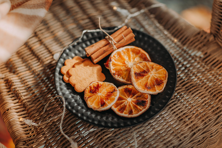 dried slices of oranges, gingerbread cookies and cinnamon sticks on black plate