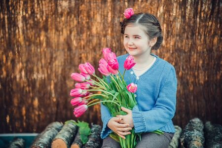 Little girl smiling happily with big tulips bouquet. Sunny day of spring, outdoor. 写真素材