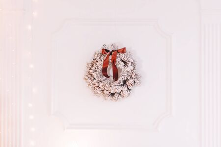 Christmas wreath hanging on the white wall