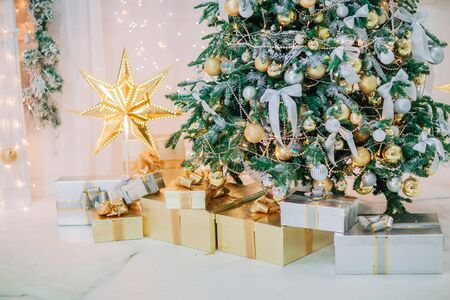 Golden christmas room party decoration. Star, presents, balls, garland and lights.