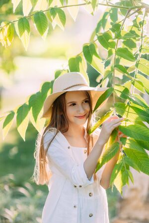 Beautiful smiling girl in white dress and hat
