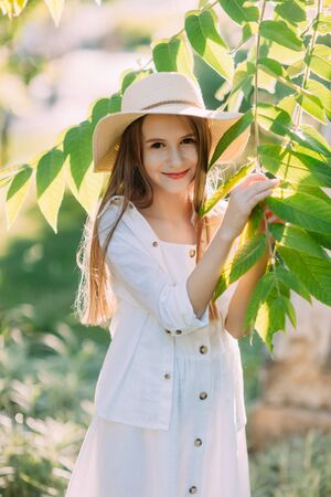 Nice little girl in white dress and hat smiling 写真素材