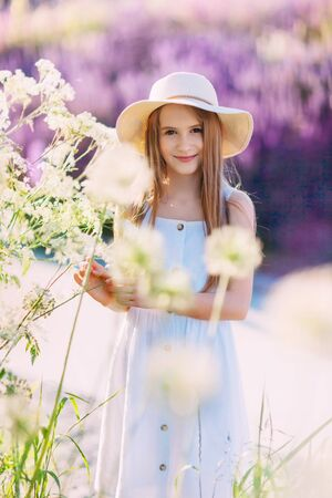 Nice smiling little girl in front of lilac background walking in the park