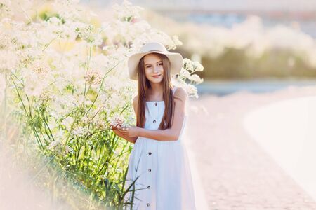 Nice little girl in white dress and hat near giant flowers 写真素材