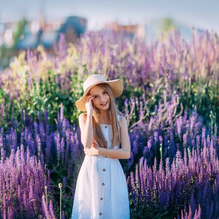 Beautiful little girl in white hat and dress smiling in the park
