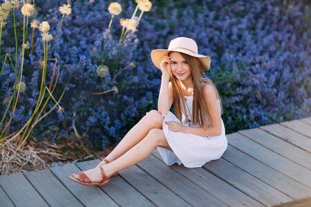 Nettes kleines Mädchen im weißen Kleid, das im Park sitzt