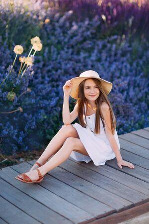 Little girl in white dress sitting in the park