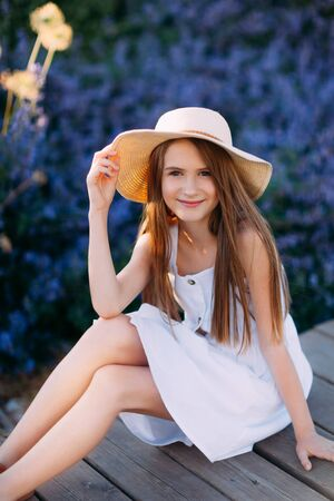 Portrait of little girl in white dress sitting in the park