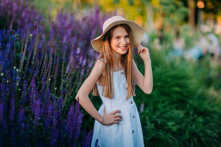 Smiling little girl in white dress in the park