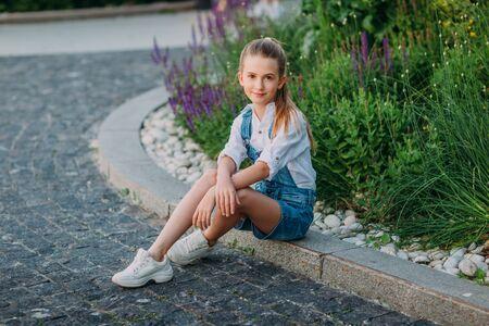Smiling little girl in white dress sitting in the park