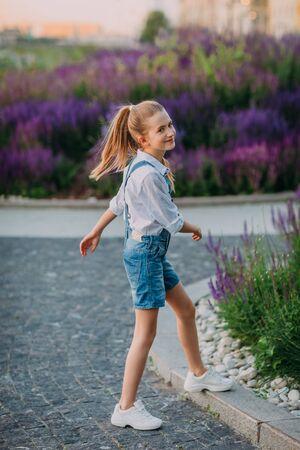 Smiling little girl in white dress walking in the park Stock Photo - 132115471