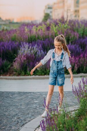 Smiling little girl in white dress walking in the park