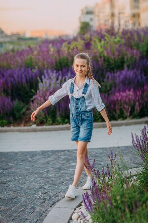Smiling little girl in white dress walking in the park Stock Photo - 132115275