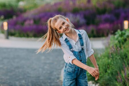 Smiling little girl in white shirt and jeans short playing in the park Stock Photo