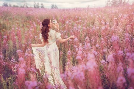 Woman with owl at field of pink flowers.