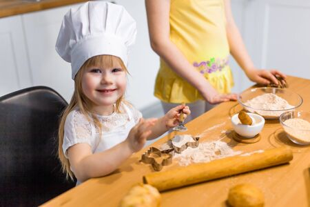 Cute little girl prepare tasty pastry, cookies and buns at home