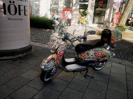 Un scooter de damas blancas de diseño colorido de pie al lado de la carretera