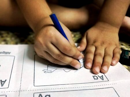 Chennai,TamilNaduIndia-070812018: A child is coloring with blue color pencil on school worksheet Stock Photo