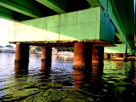 Pillar of a over bridge from lower angle with reflection of running water