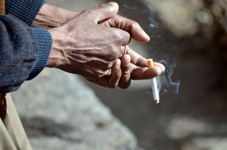 manos sucias: Manos viejo y polvoriento que sostienen cigarrillo recién encendido