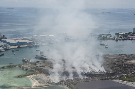 polution: Burning garbage heap of smoke from a burning pile of garbage on island. Stock Photo